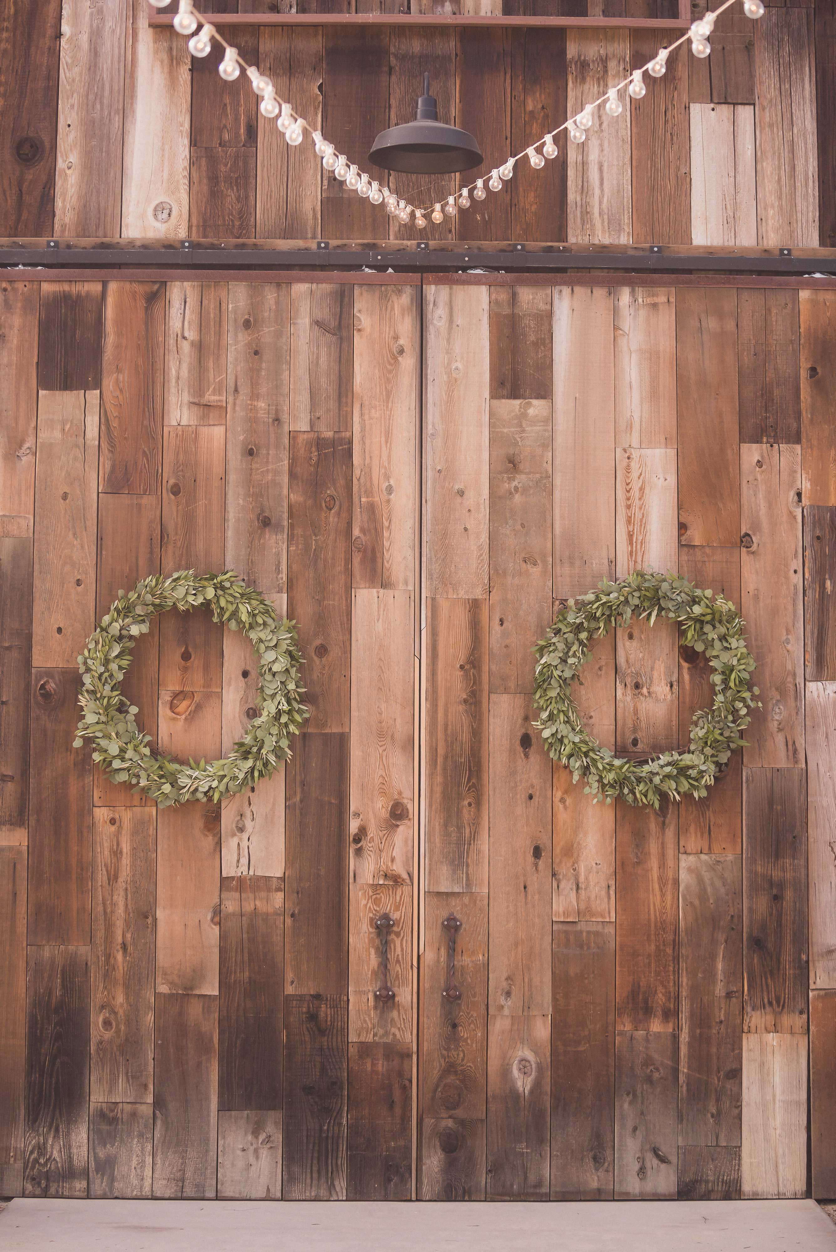 Two greenery wreath arrangements on rustic vintage barn door for wedding reception