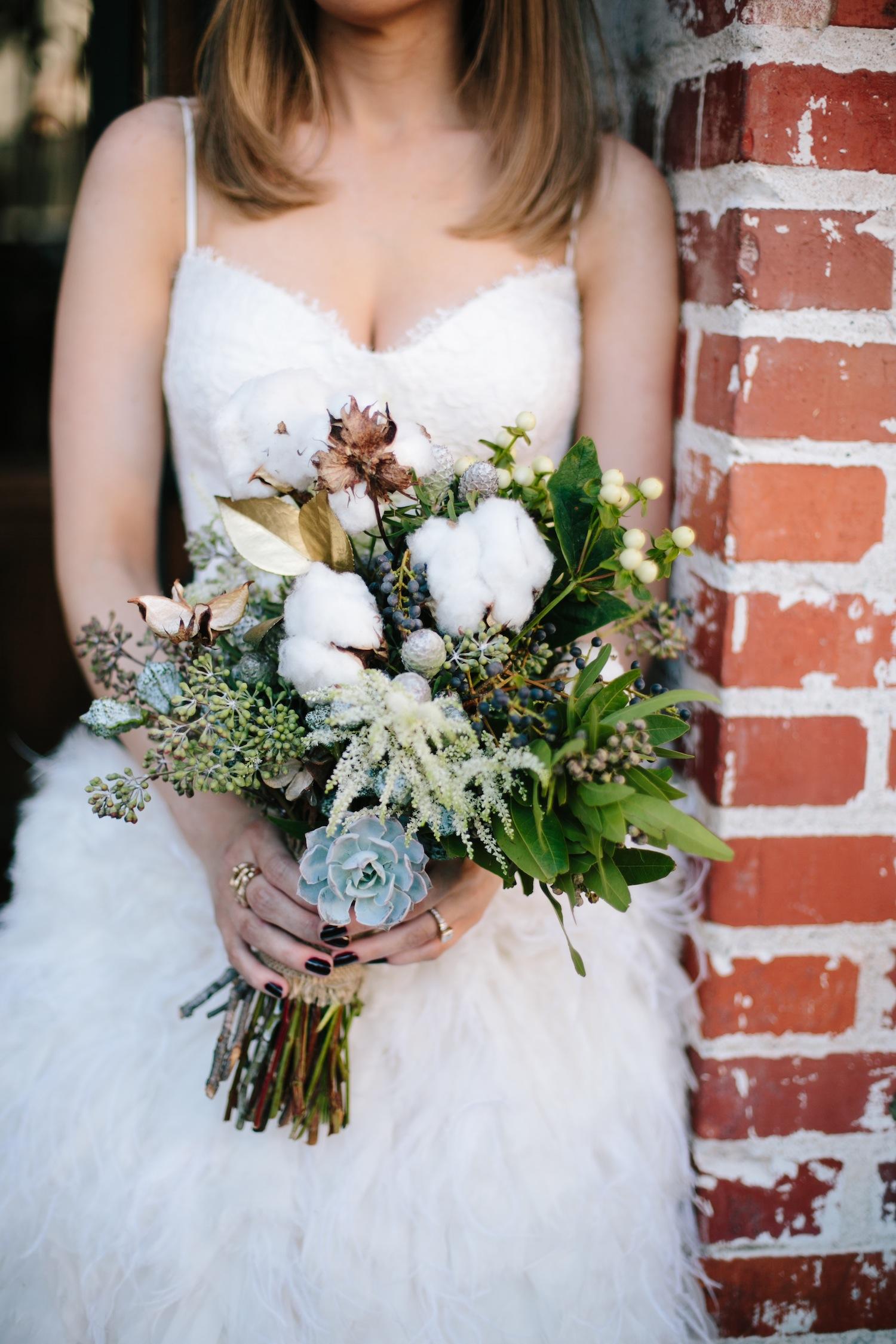 Bride in Monique Lhuillier gown holding winter wedding bouquet succulent cotton gold leaves