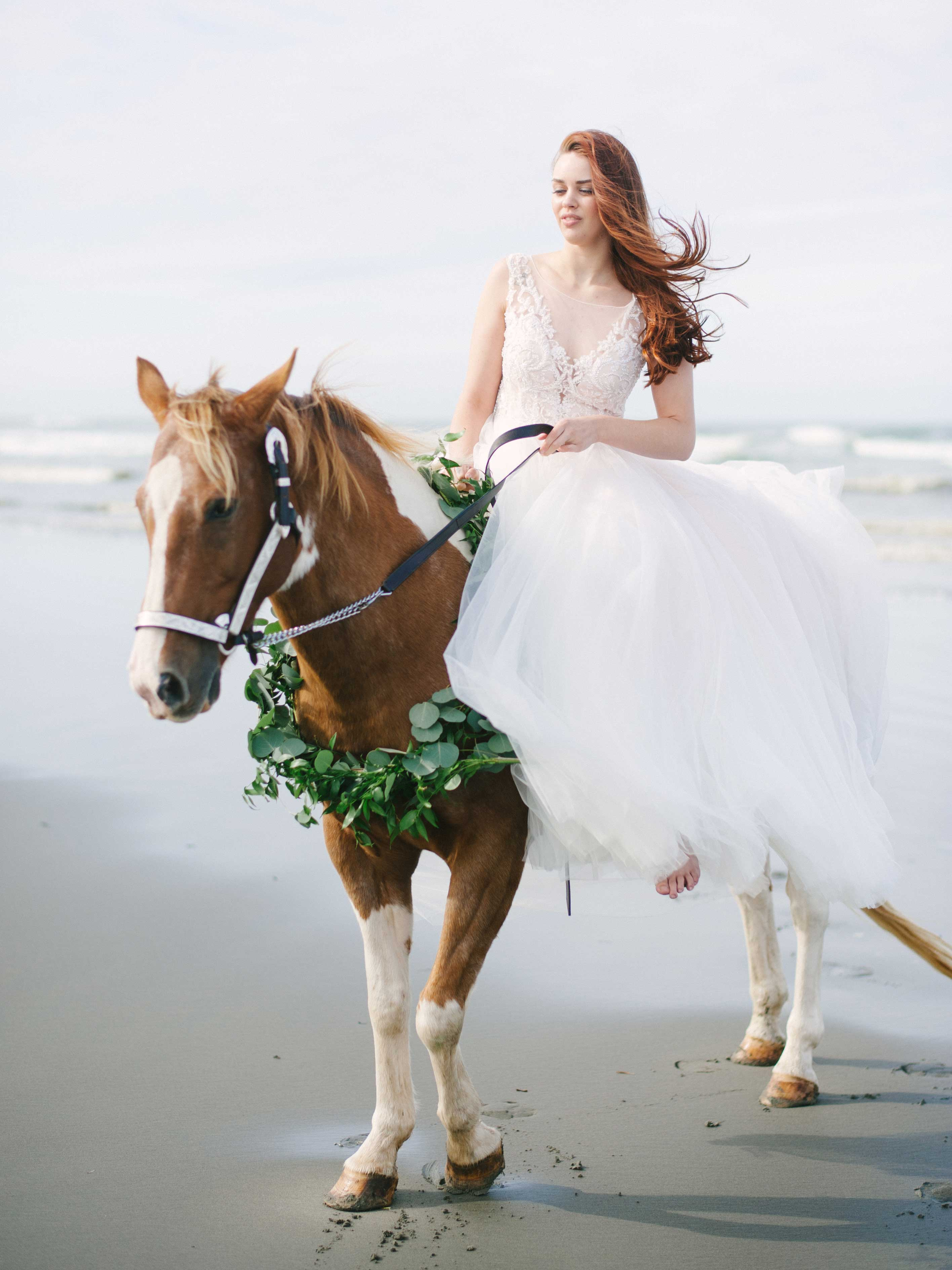 Greenery wreath around horse neck on beach bride transportation