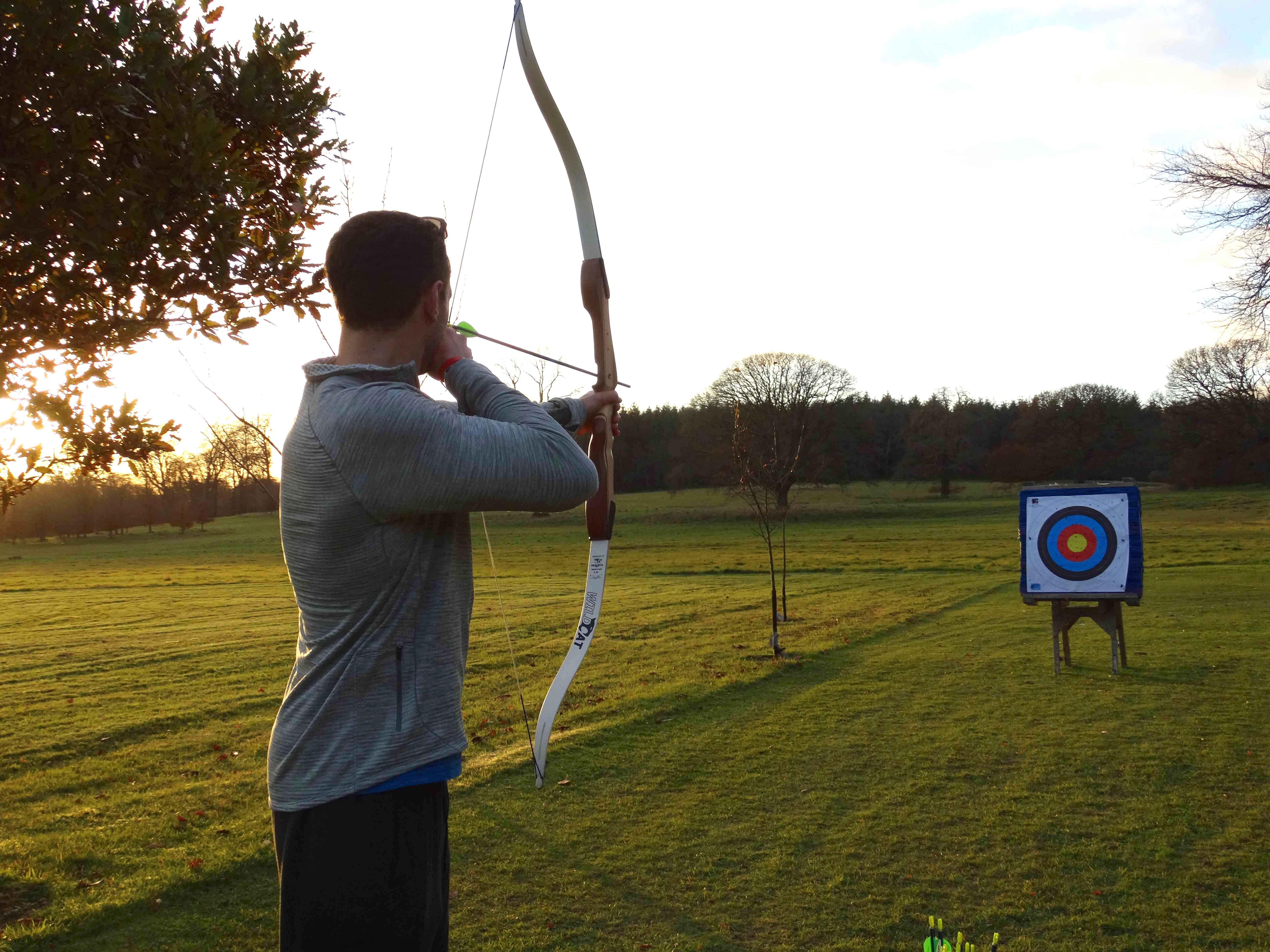 Newlywed groom partaking in archery at Ballyfin House in Ireland