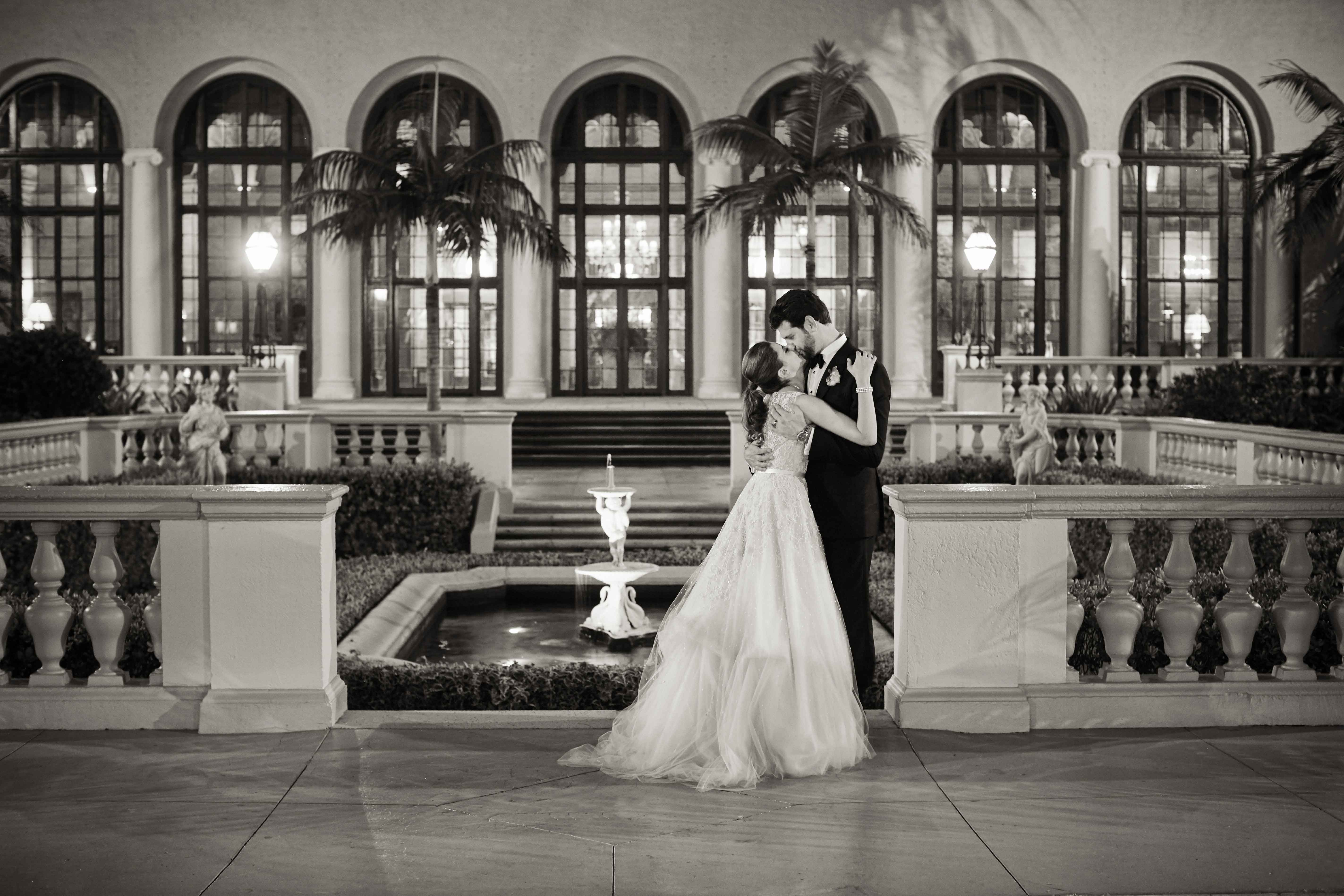 Black and white photo of bride and groom in front of The Breakers Inside Weddings winter 2017 issue