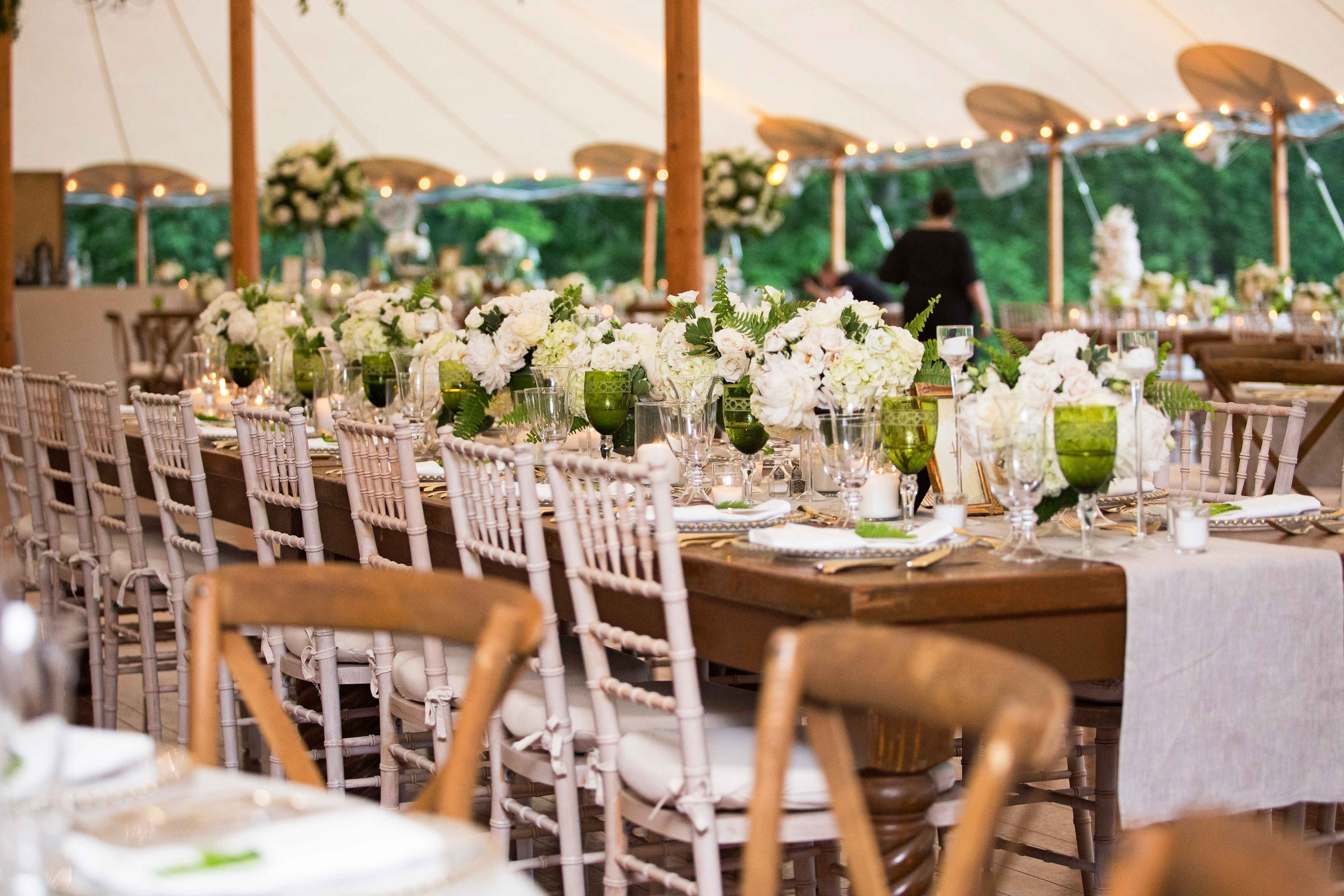 Tent wedding rustic wood tables with green and white flowers green glassware