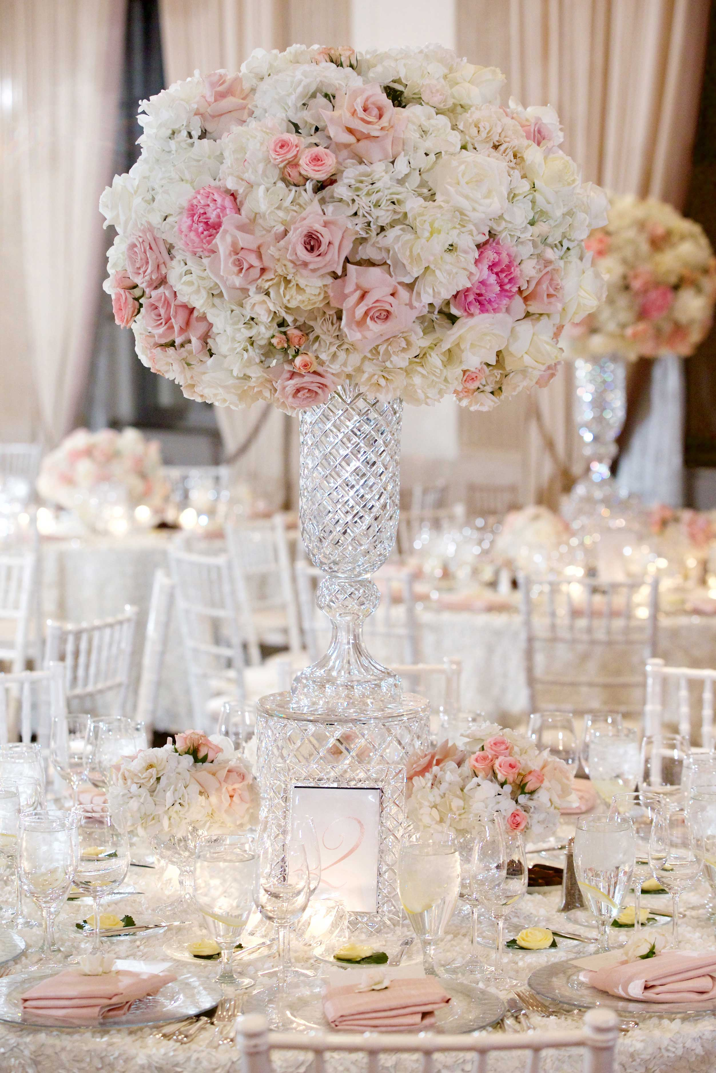 White and pink flower centerpiece in tall crystal riser vase Inside Weddings winter 2017 issue