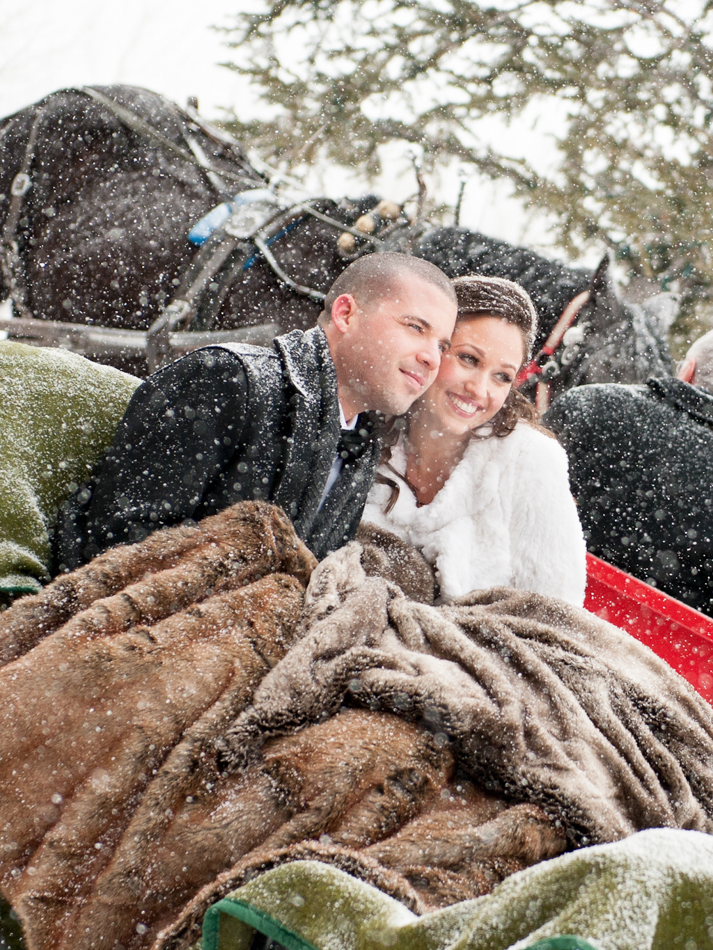 bride and groom with furs on horse-drawn carriage in snowstorm winter wedding