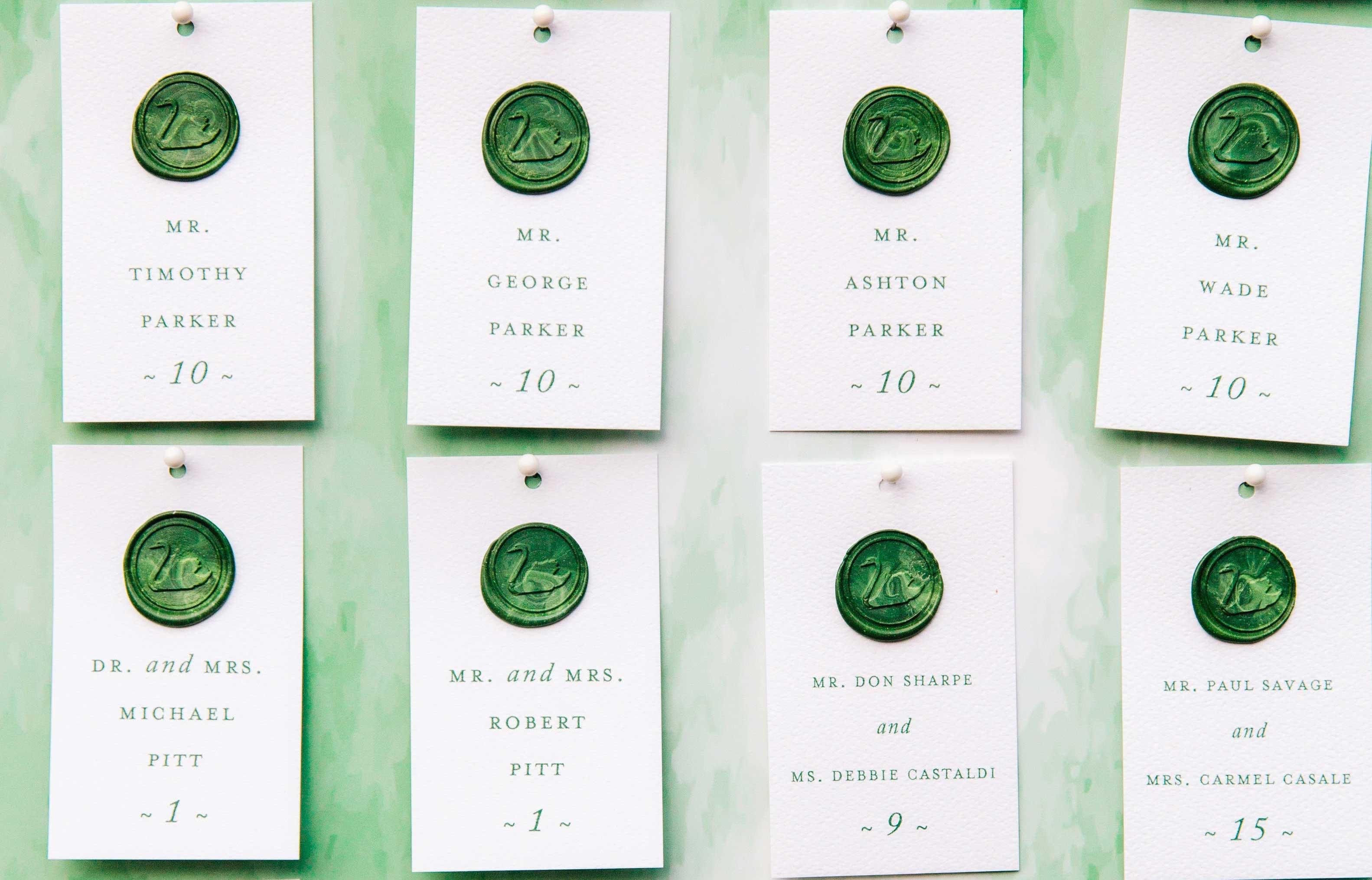 Dark green wax seal escort cards on green board wedding ideas
