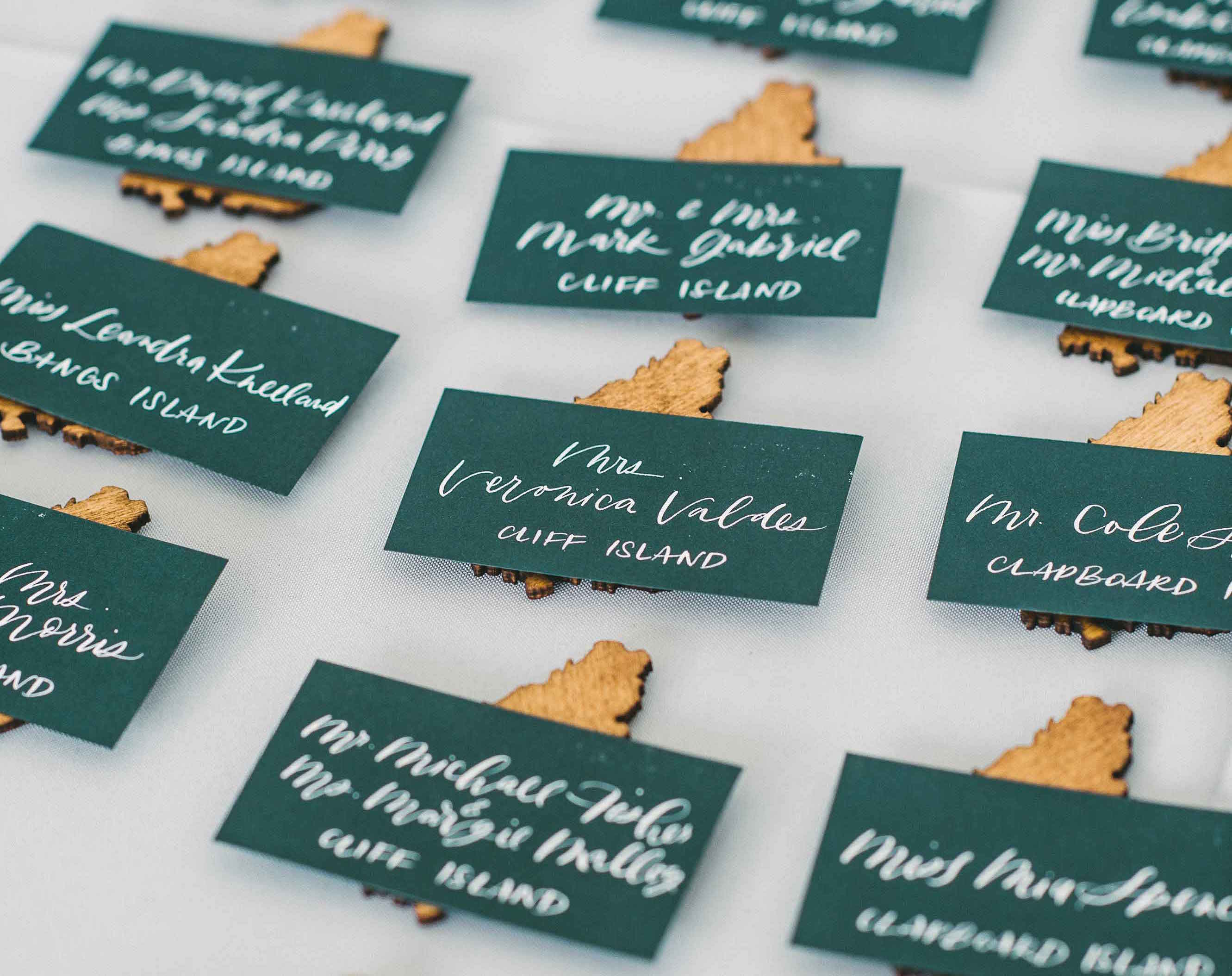 Dark green calligraphy escort cards on wood pieces