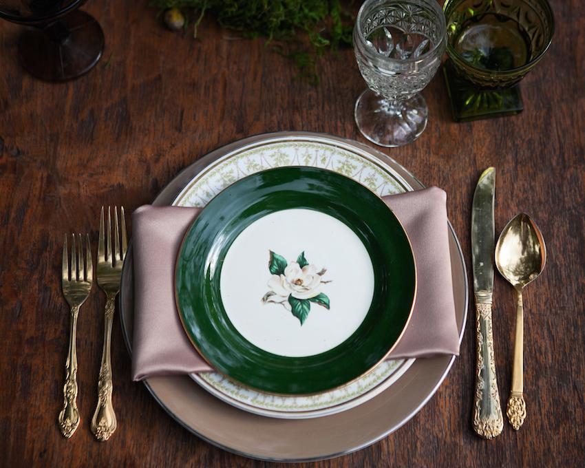 Dark green china plate rim at place setting dark wood table