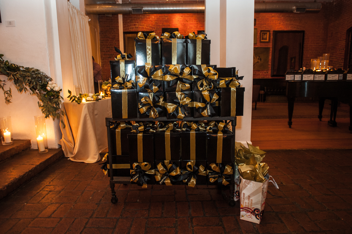 black gift boxes with gold ribbon filled with wedding favors