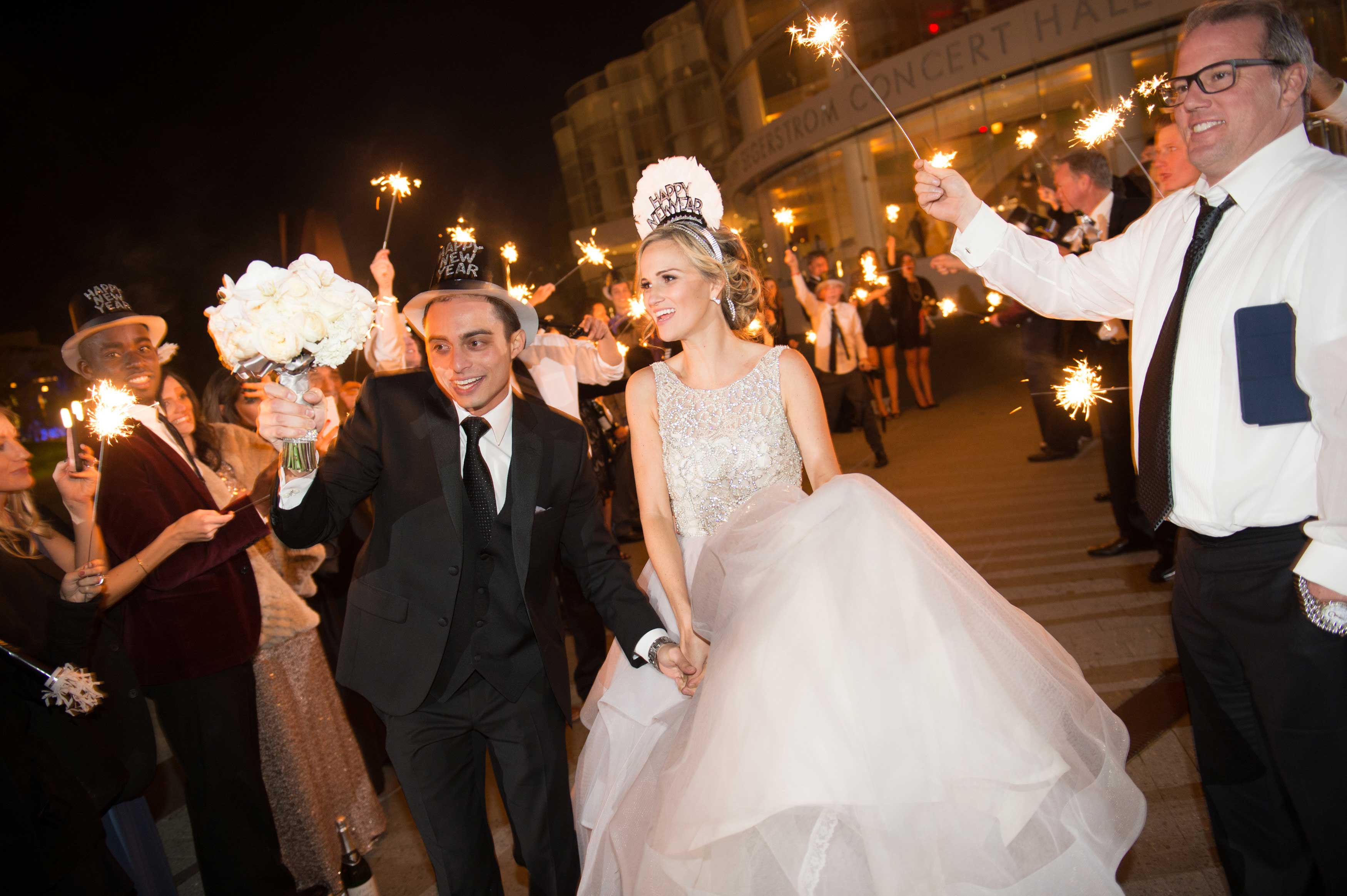Bride and groom in New Year's Eve tiara hats and headbands sparkler exit