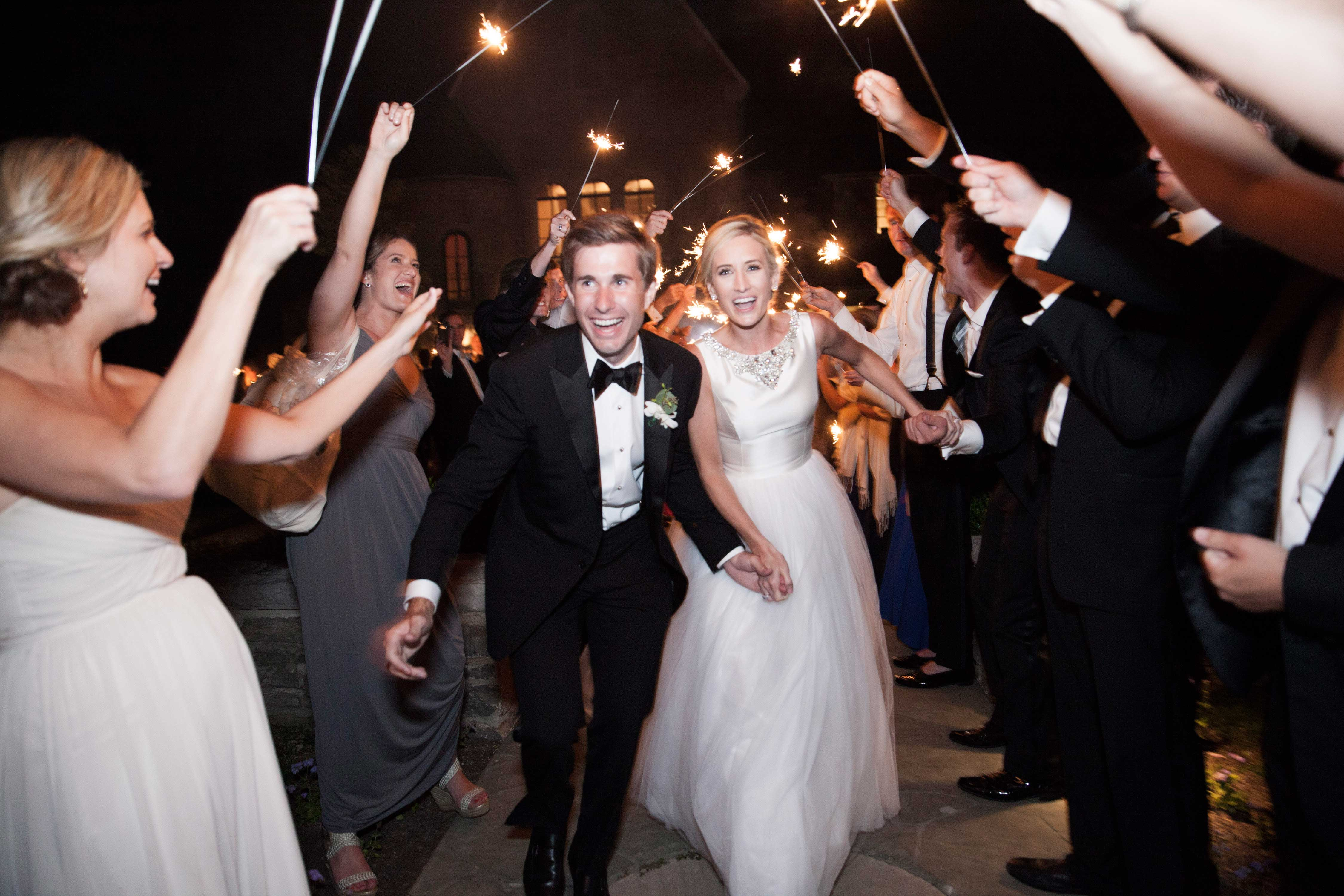 Bride and groom running through tunnel of guests holding sparklers exit