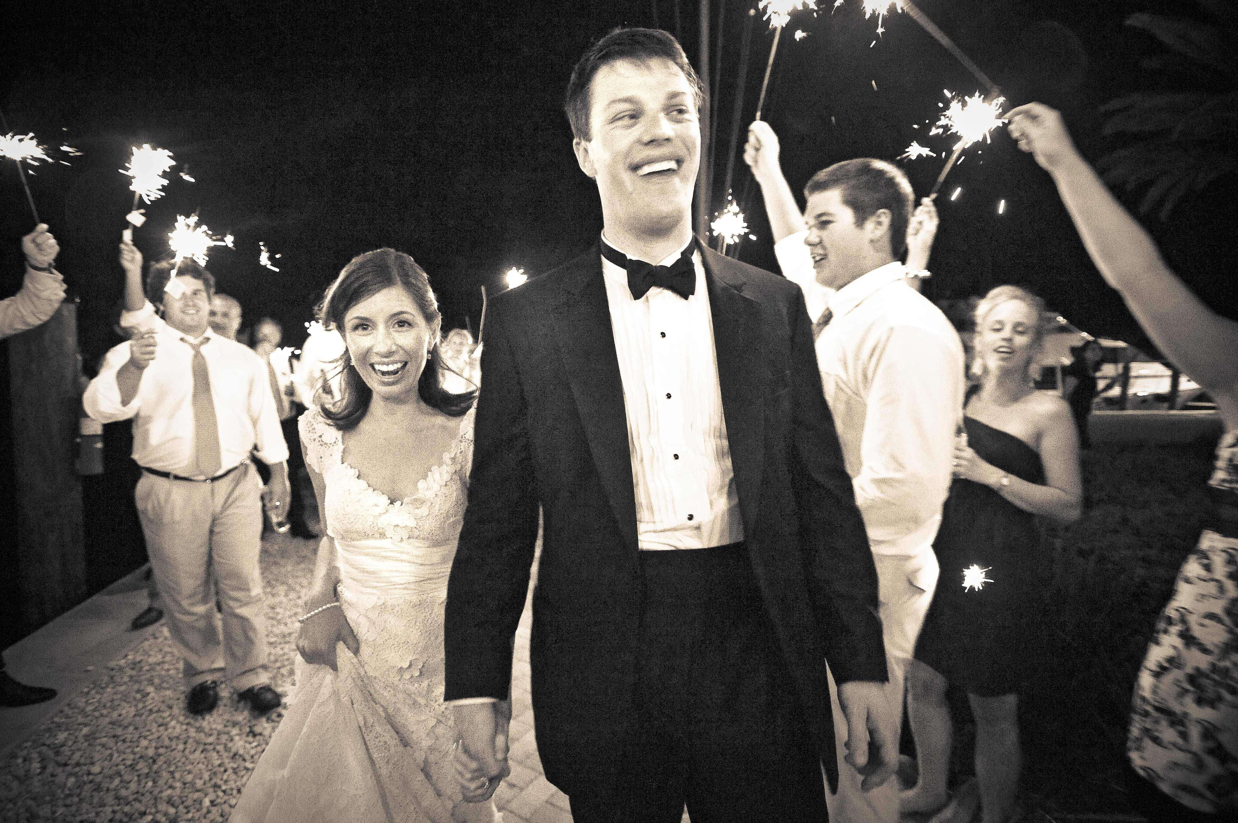 Black and white photo of bride and groom surprised happy sparkler exit