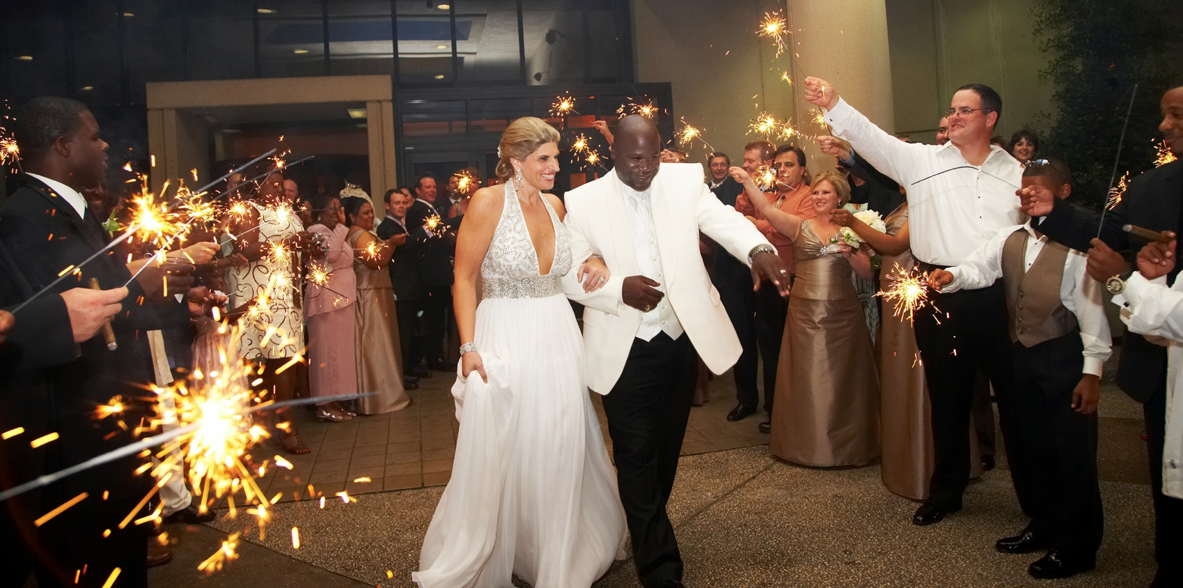 Bride and groom walk out of reception with sparkler exit