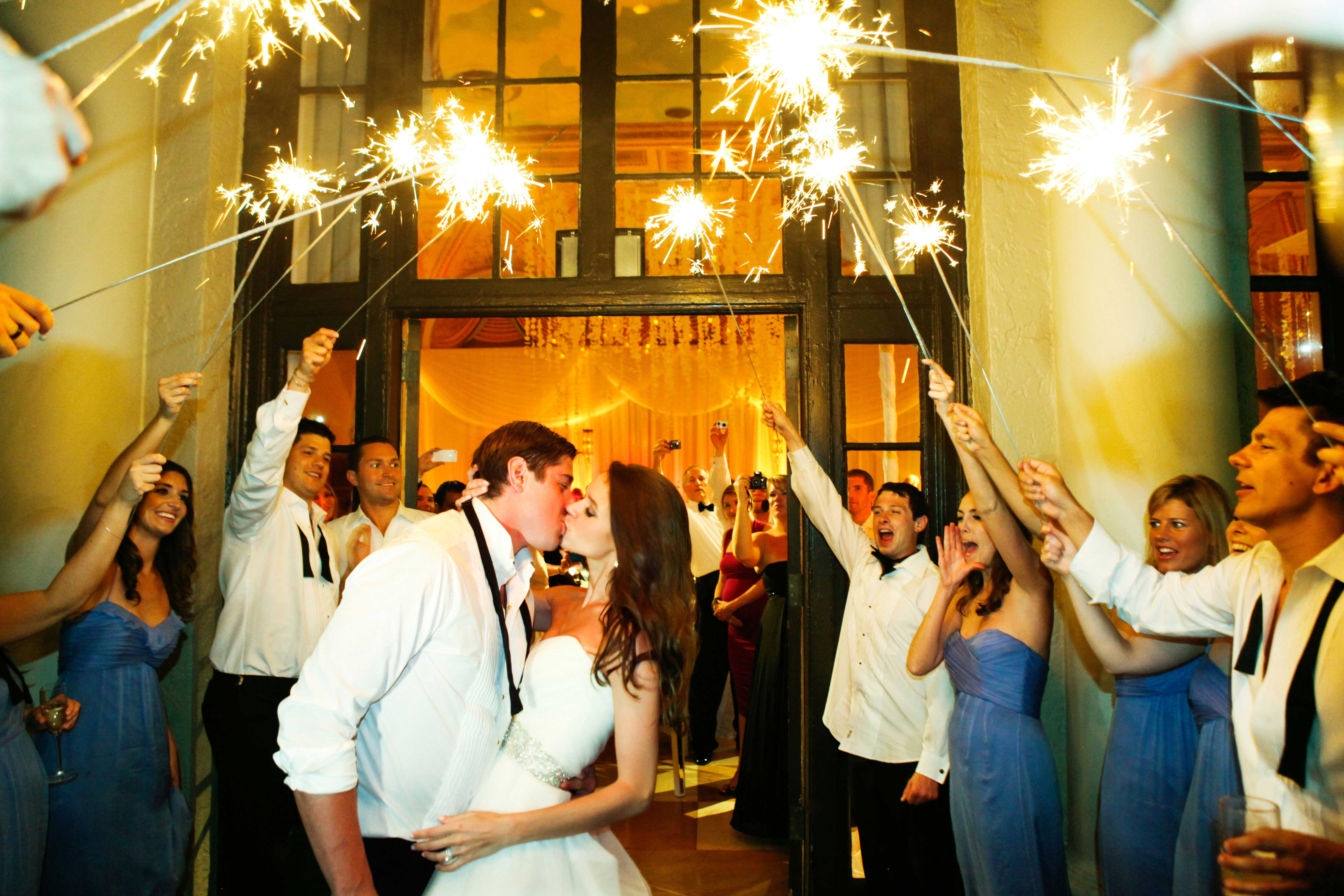 Bride and groom kiss at wedding reception sparklers guests taking photos