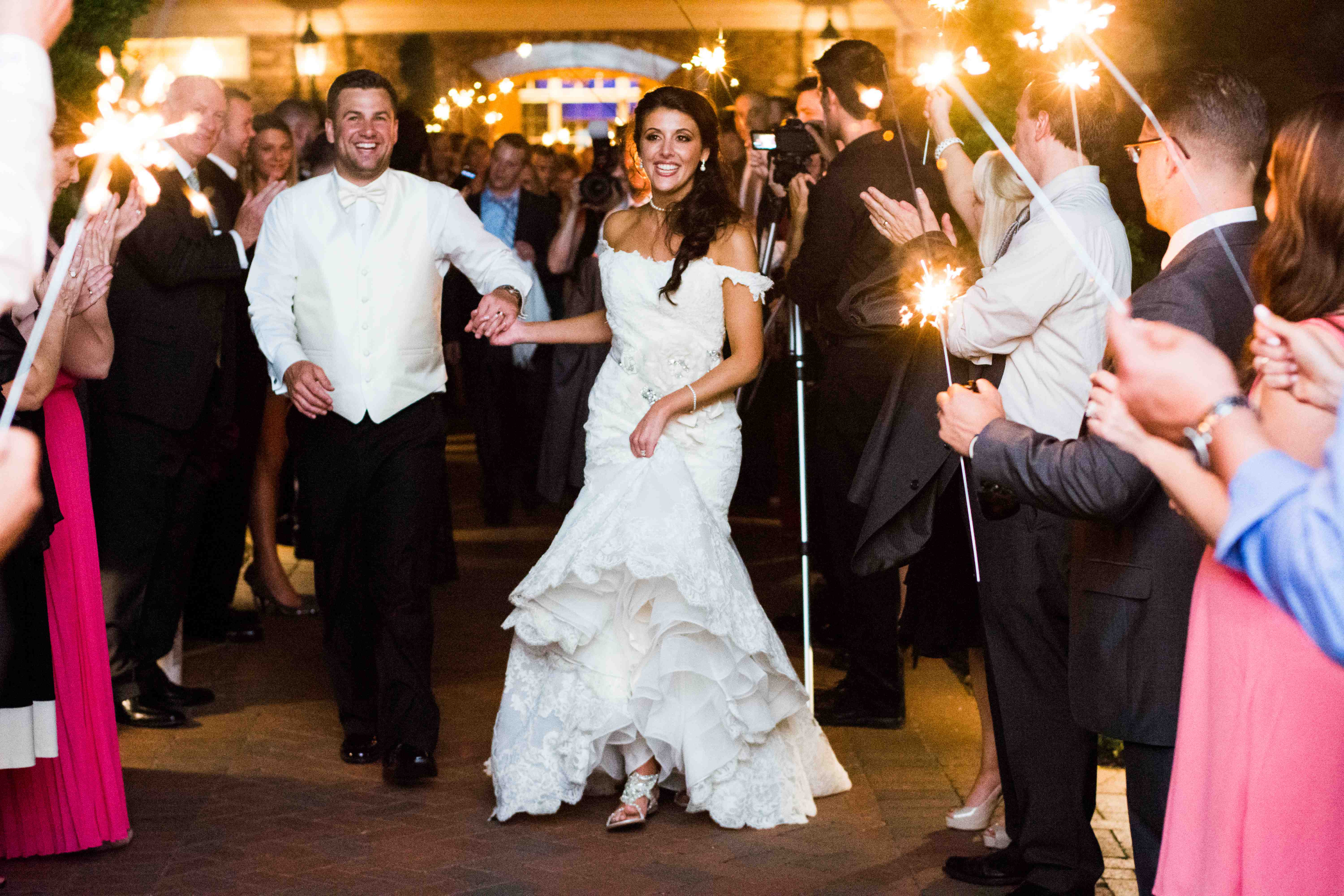Bride and groom smile and run through tunnel of guests waving sparklers sparkler exit