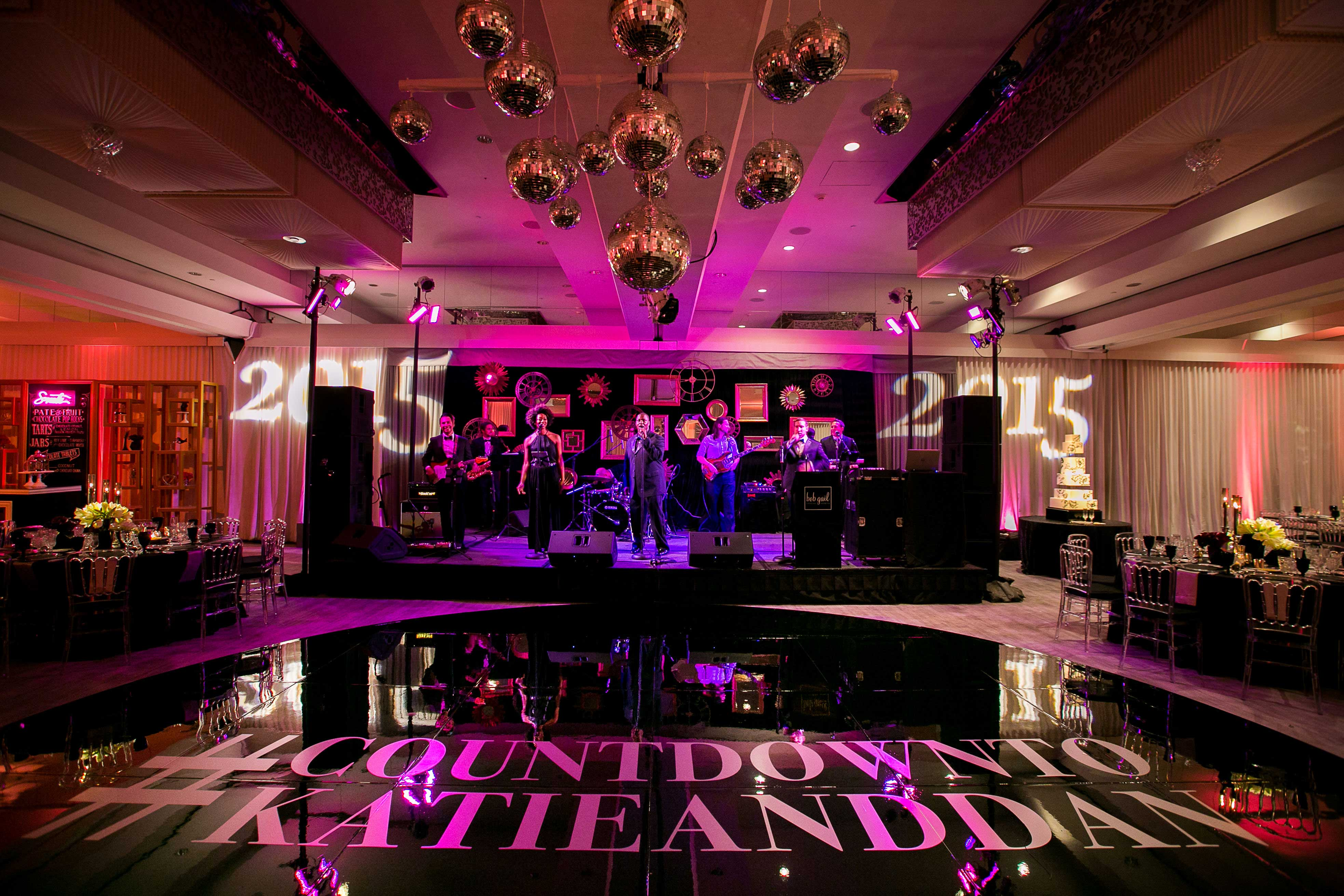 Vibrant fuchsia pink and black dance floor for New Year's Eve wedding reception live band stage