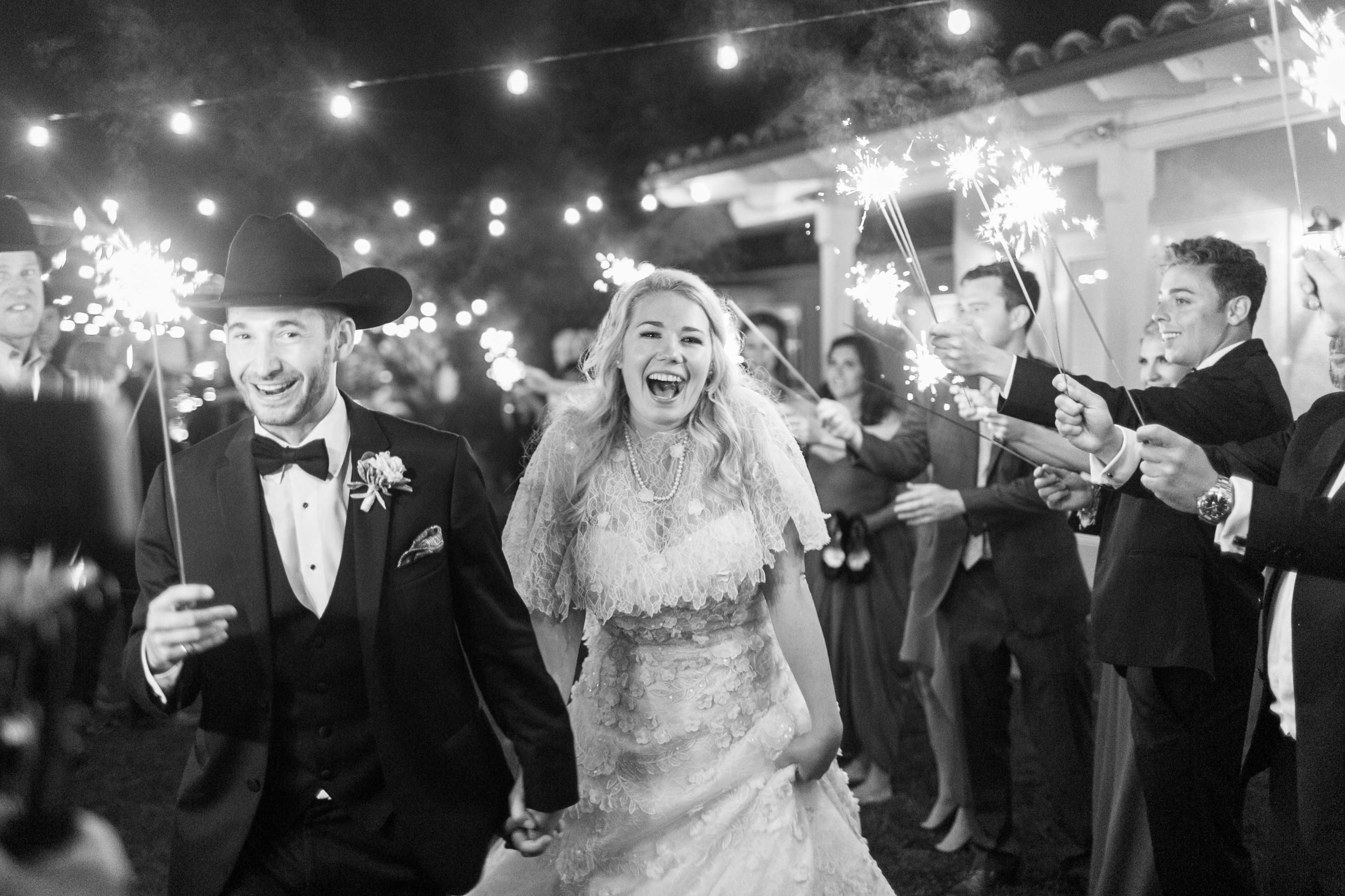 Black and white photo of sparkler exit smiling bride and groom in cowboy hat