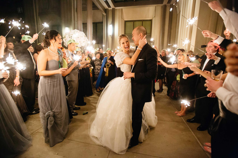 Bride wearing fur wrap hugging groom during sparkler exit new year's eve wedding