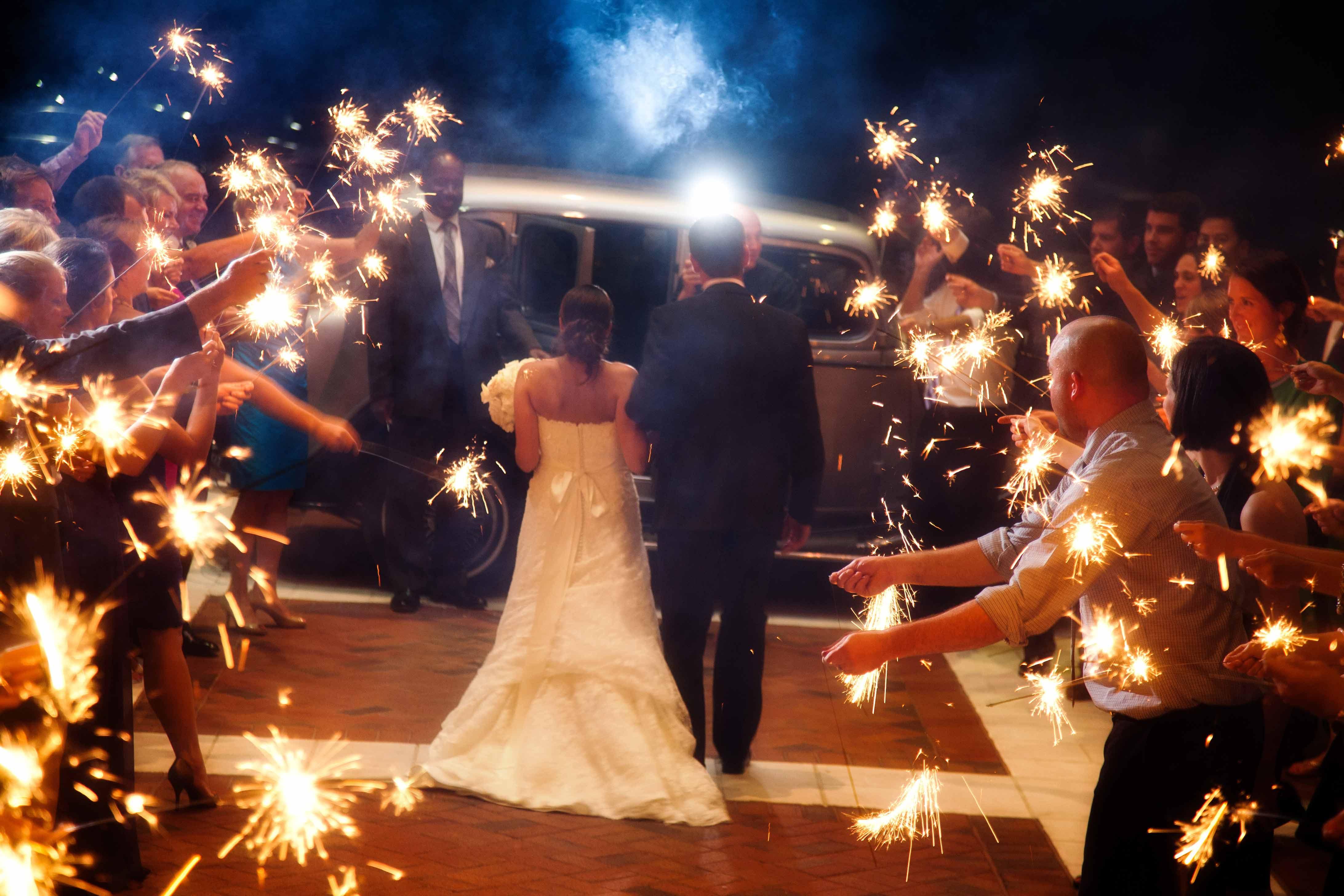 Bride and groom walking towards getaway car sparkler exit at night reception