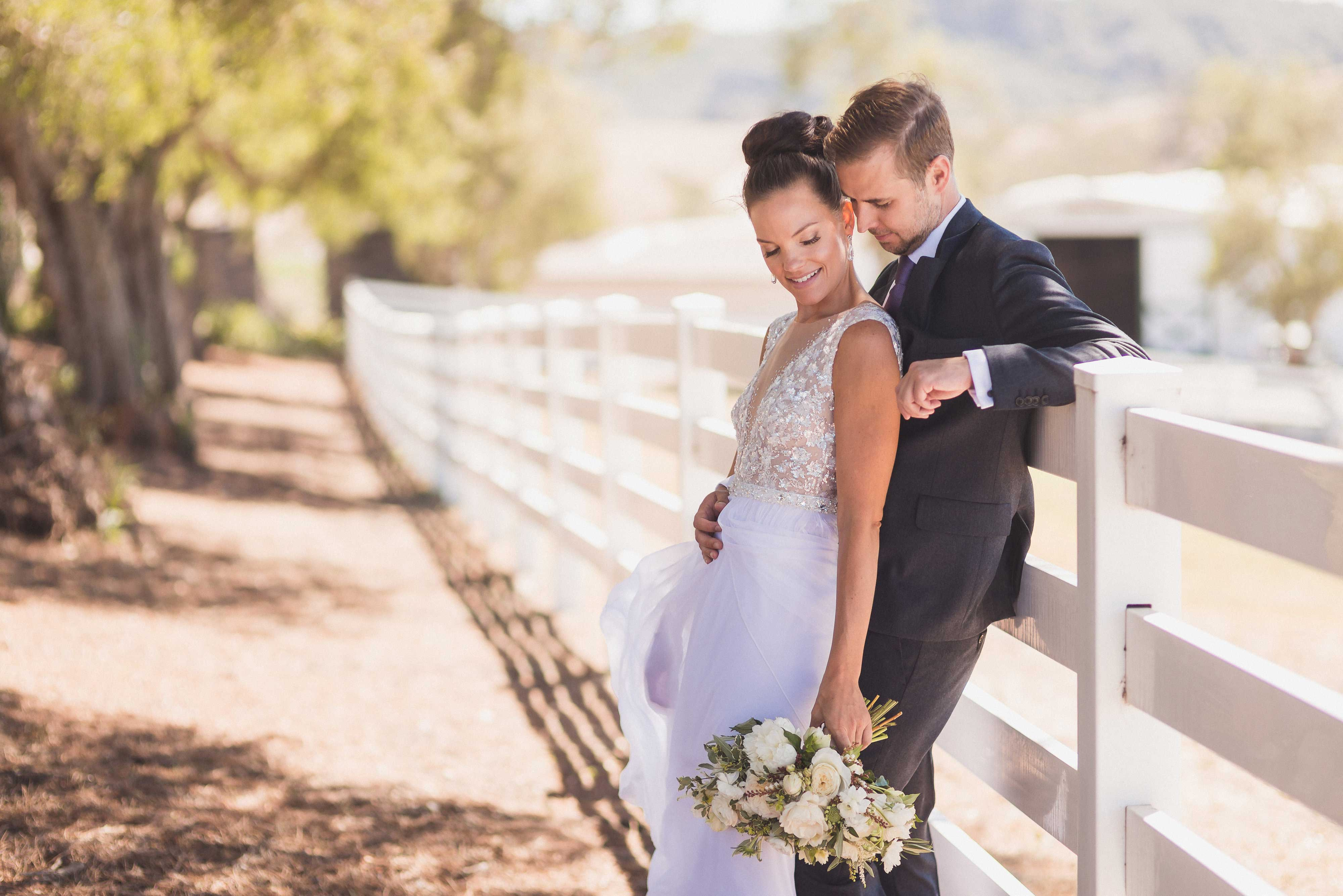 Bride In Dress From Carines Bridal With Husband By White Picket Fence