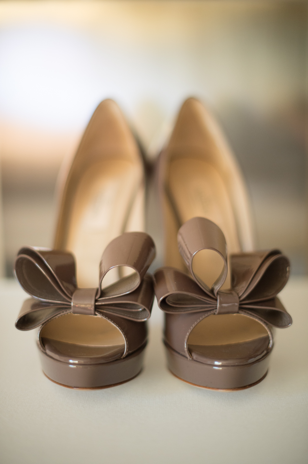 brown patent leather pumps with bows at the toe, neutral bridal shoes