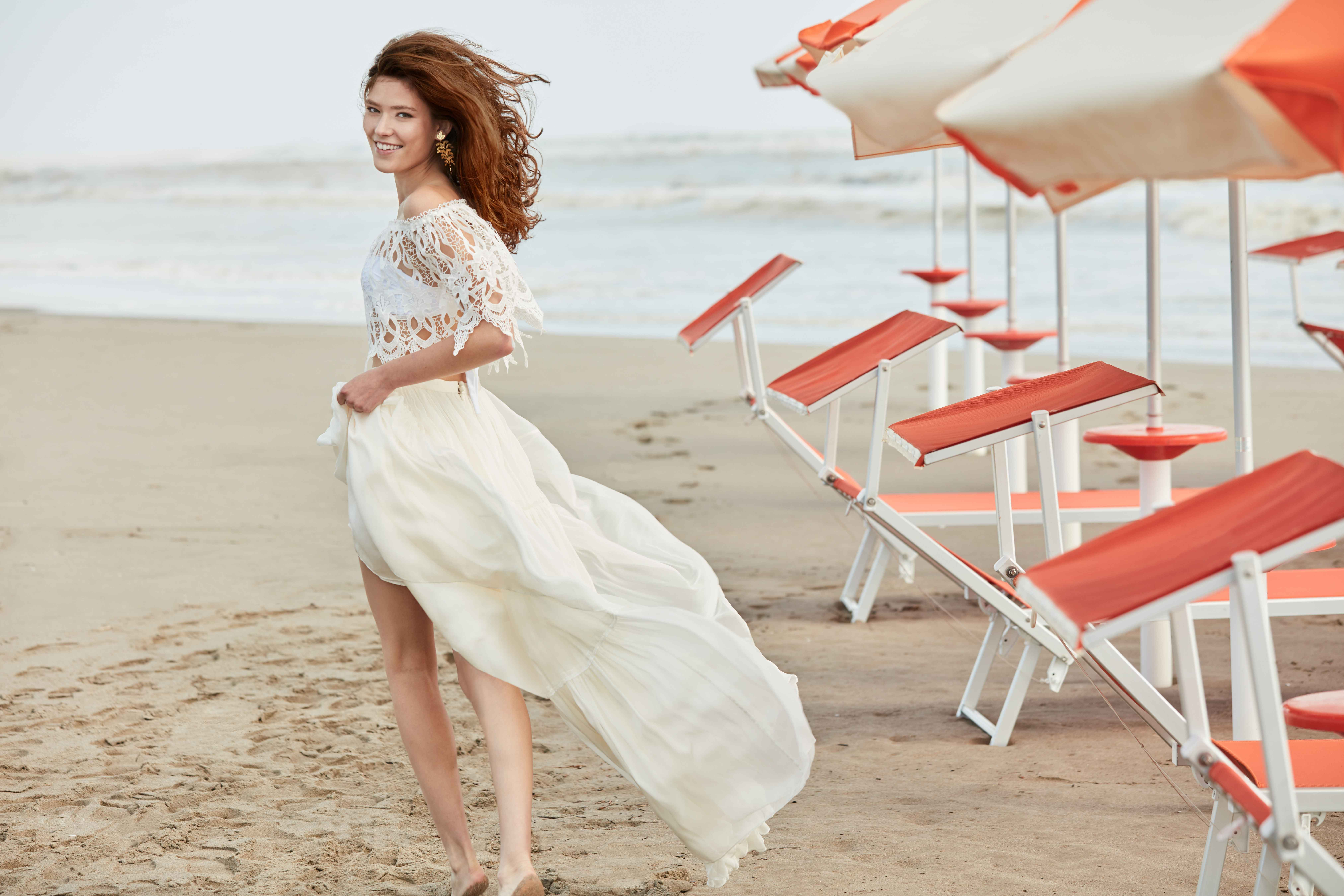 Bride on honeymoon in bandeau swim suit with lace cover up top and skirt BHLDN Malta topper, carol bandeau, agatha skirt