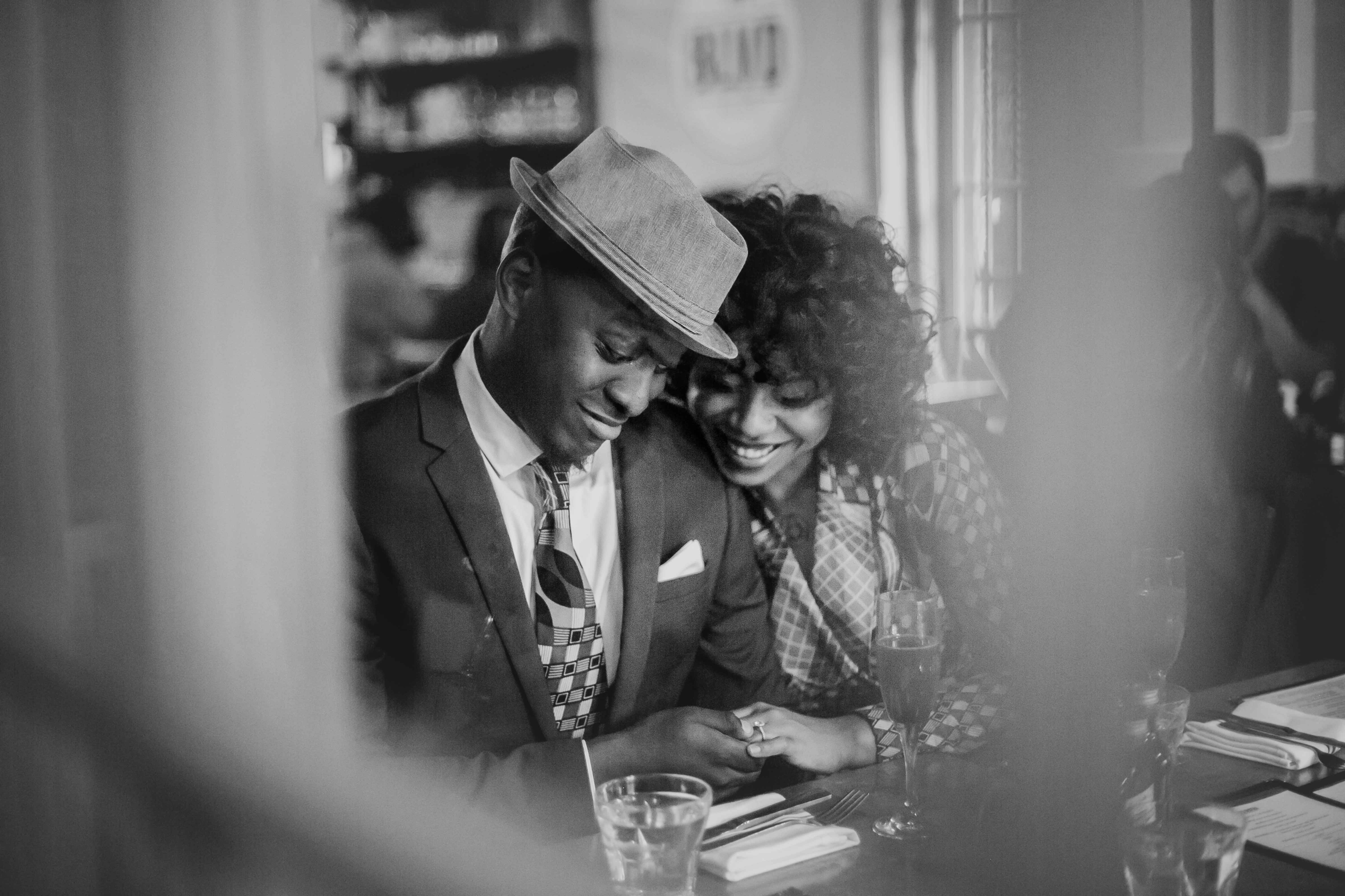 Black and white engagement session photo at restaurant through window couple looks at engagement ring