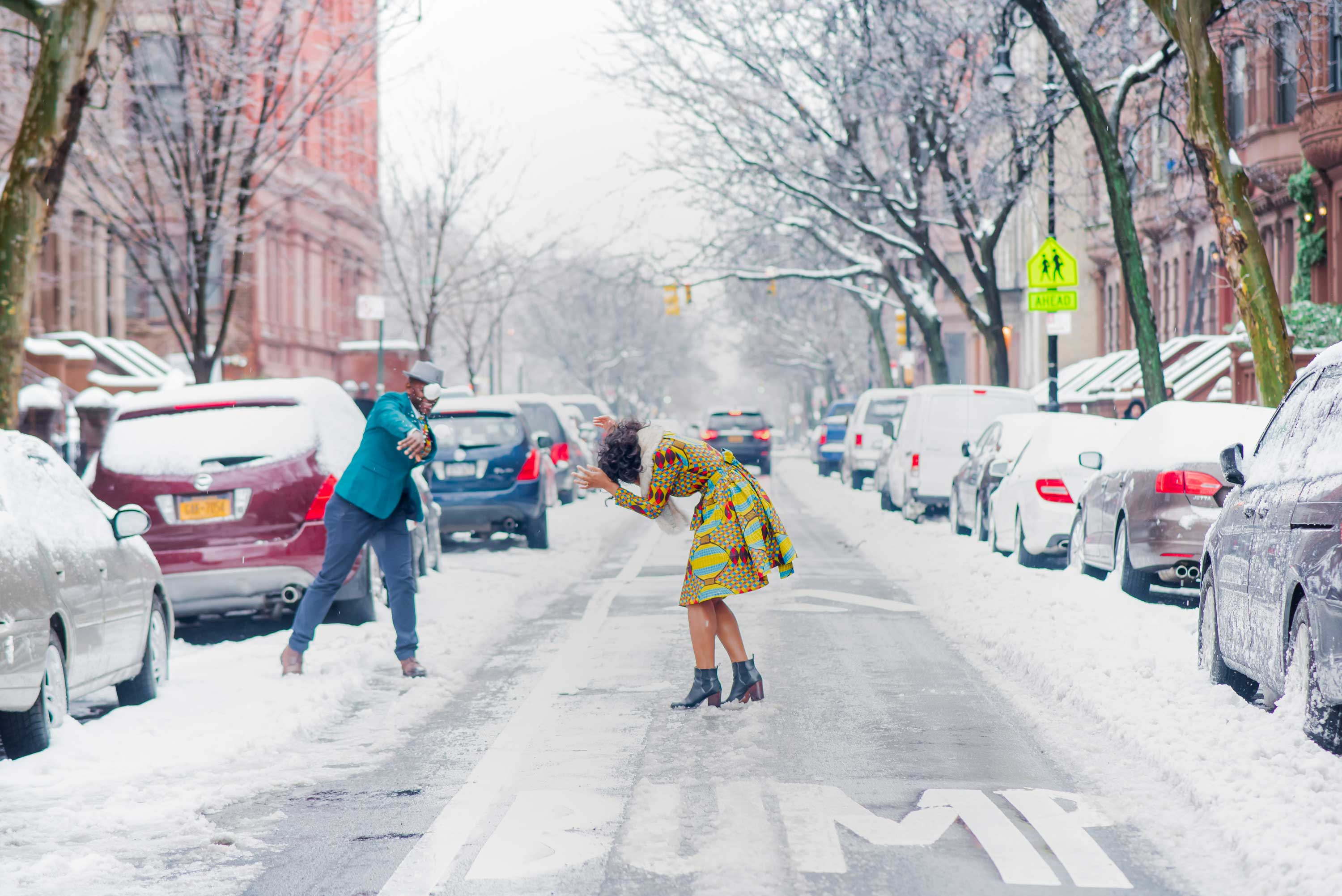 Snowball fight in New York City neighborhood snowy engagement photo session