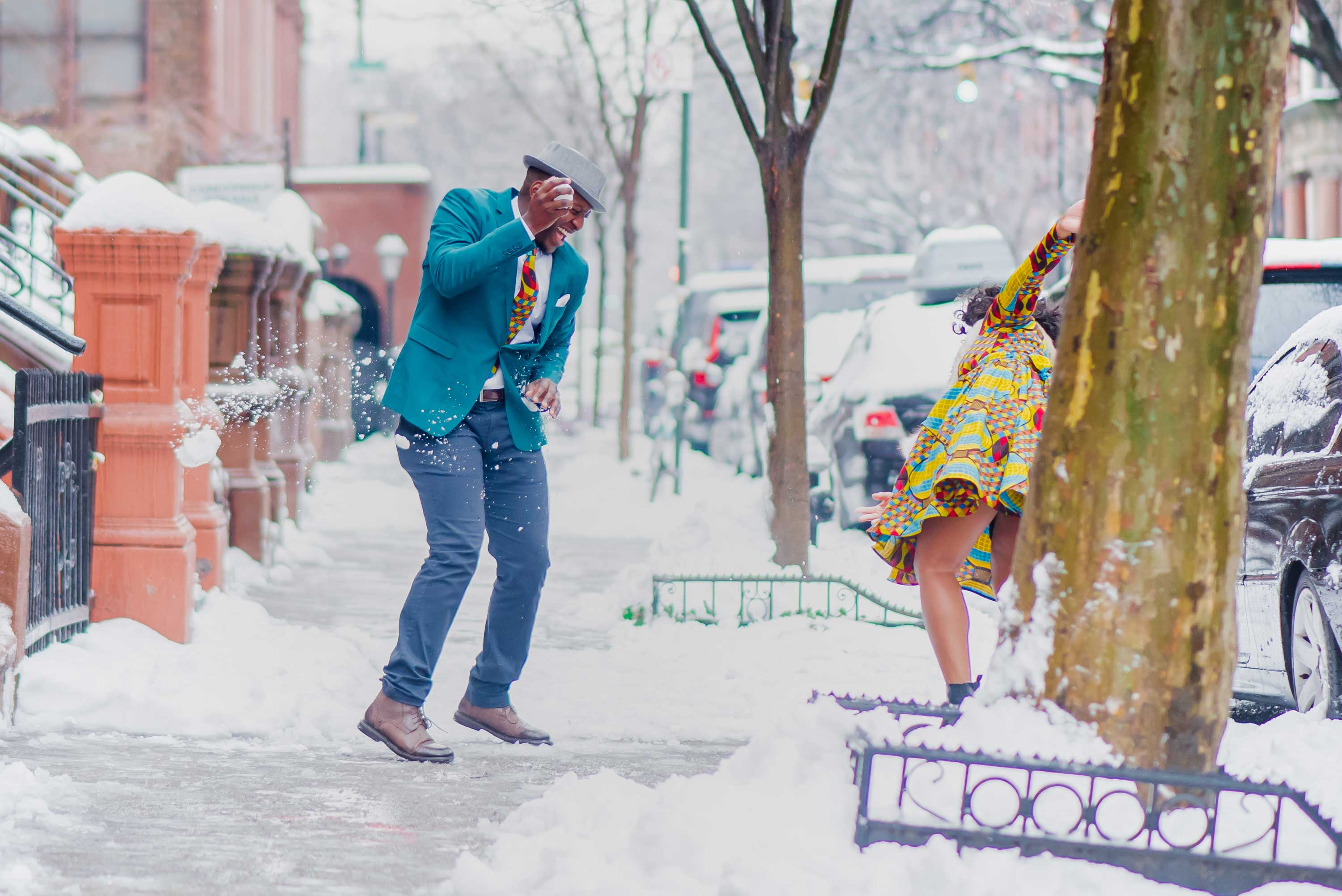 Groom to be laughing throwing snowball at bride to be engaged engagement session snowy new york city