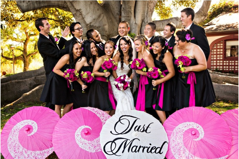 "wedding party leans in together, pink paper umbrellas read ""just married"""
