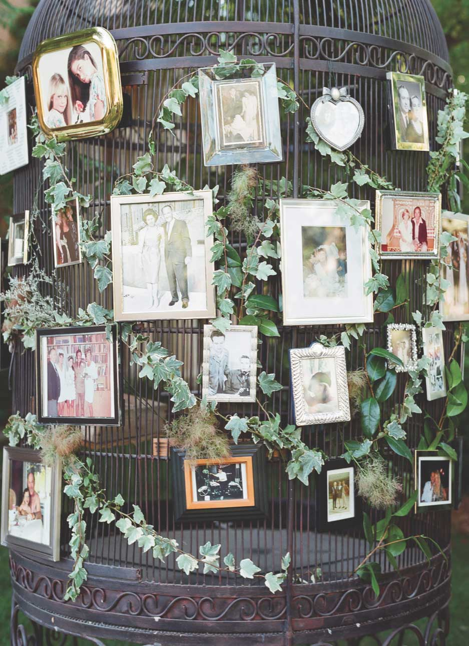 Large bird cage with framed family photos at wedding ceremony reception outdoors alfresco