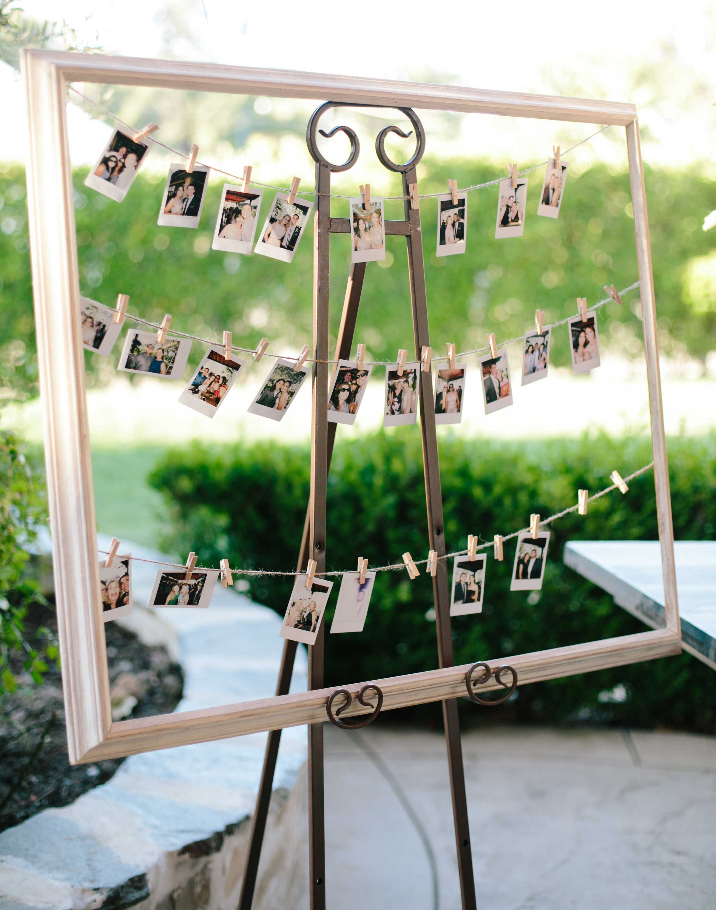 Family photos polaroids on twine with clothespins wedding reception ceremony outdoor