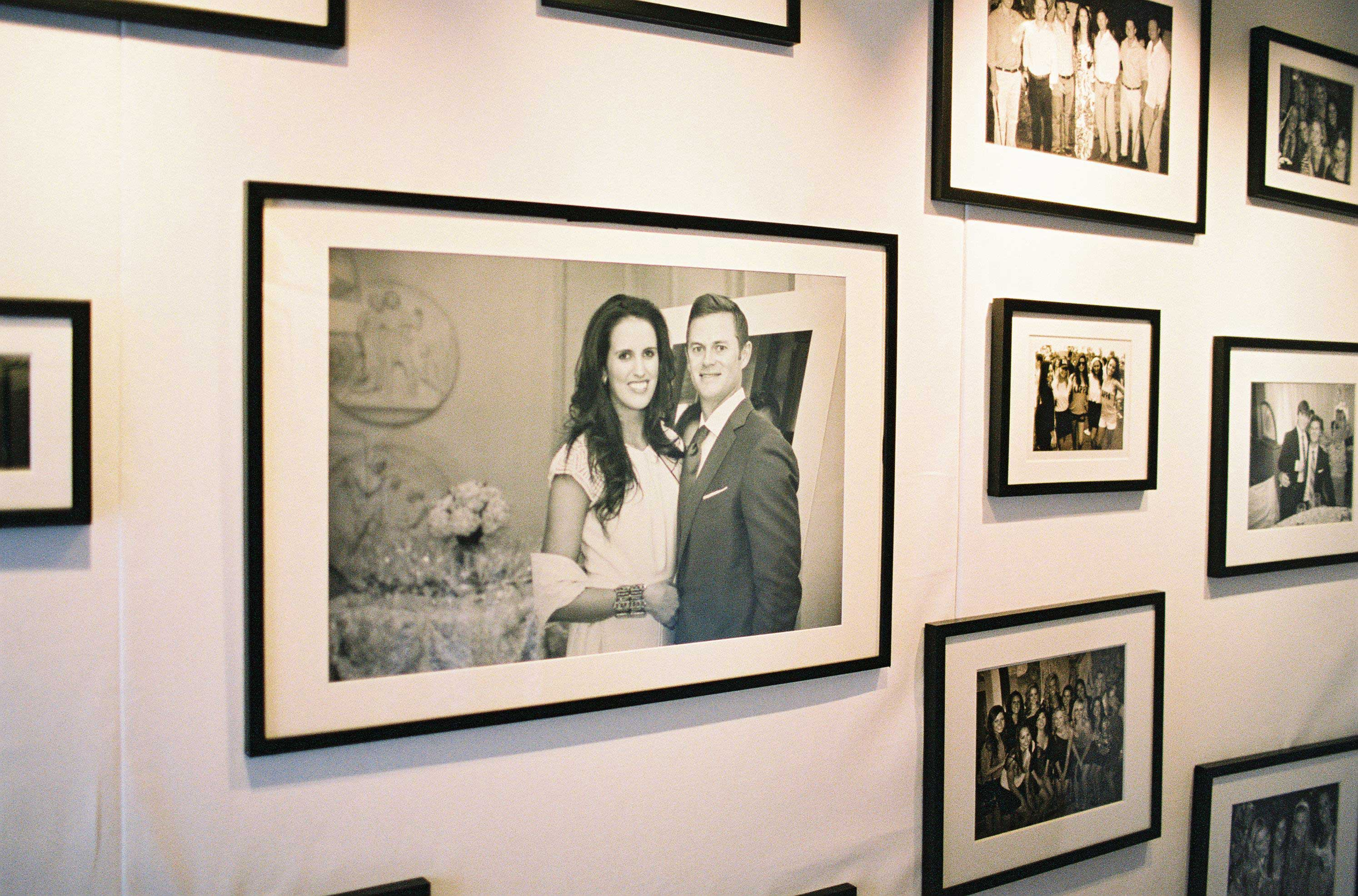 Framed photos of couple and family on gallery wall at rehearsal dinner