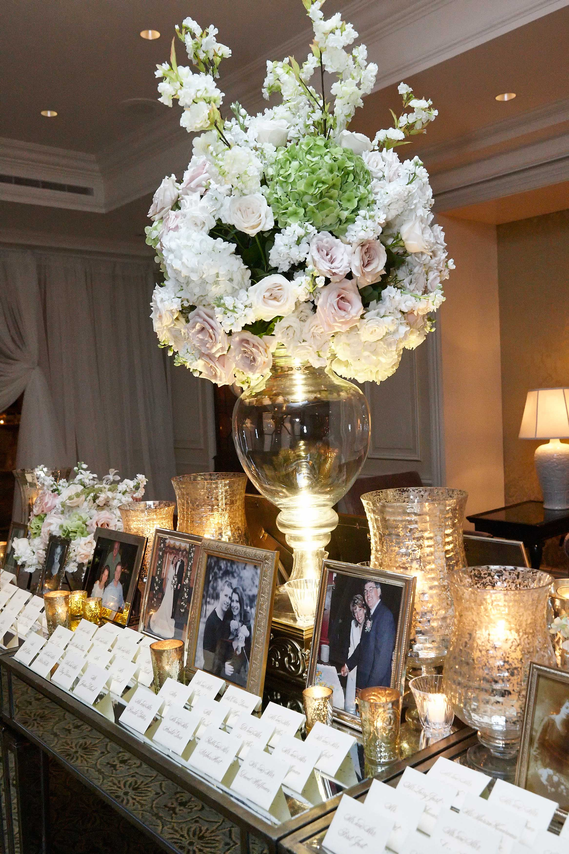 Mirror escort card table with place cards and photos of family members in frames