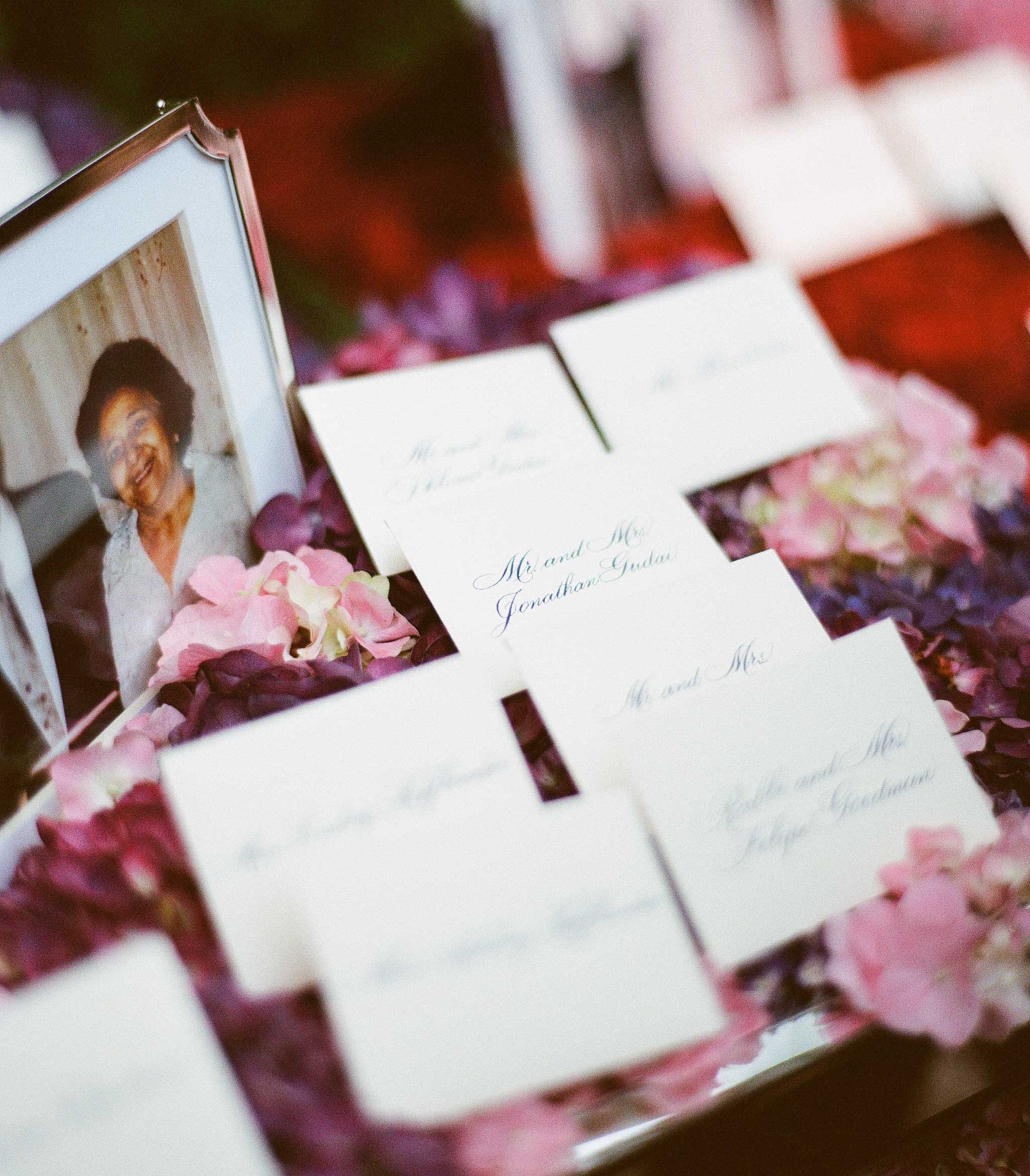 Escort cards on flower petals with photos of family members on table