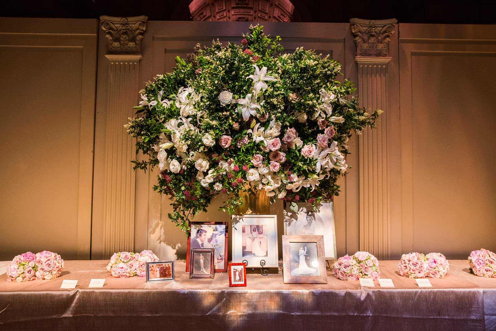 Escort card table with tree centerpiece and family photos in center of table