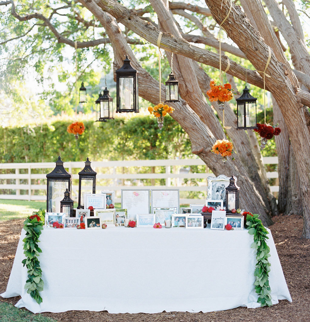 Outdoor wedding table with family photos under tree lanterns bright flowers