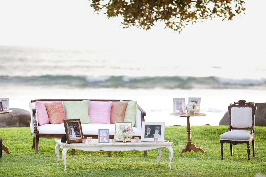 Outdoor oceanfront lounge area with sofas and framed family photos on coffee table
