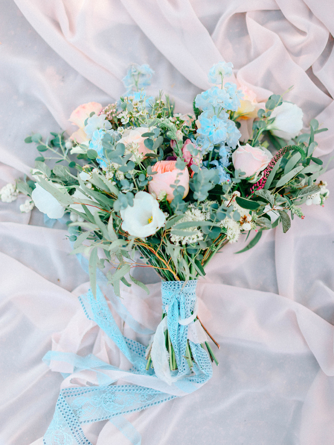 bouquet with peach and light blue flowers with greenery leaves tied with blue lace ribbon elopement