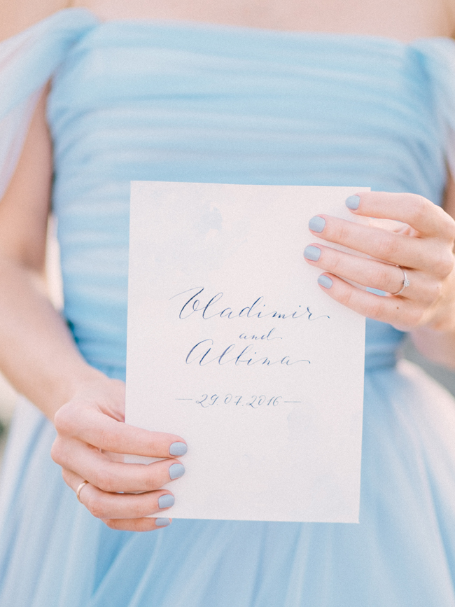 Bride with light blue wedding dress baby blue manicure holding card with her name in calligraphy elopement