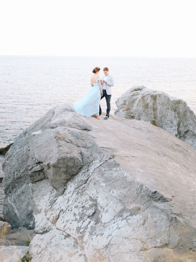 Bride and groom read letters to each other overlooking the ocean sea on rocks Crimea light blue wedding dress