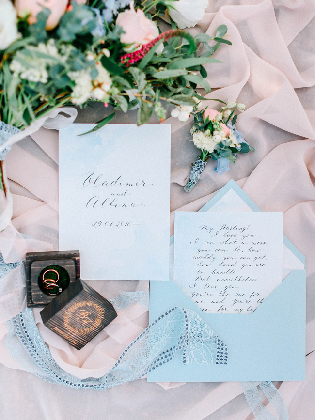 Wood ring box and love note in light blue envelope for elopement