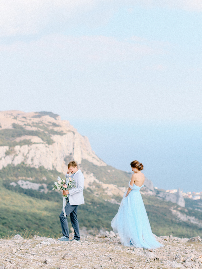 Romantic cliff top elopement in Crimea bride in light blue off shoulder wedding dress groom holding bouquet