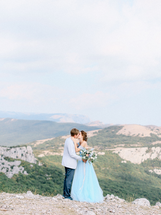 Crimea cliff top elopement light blue wedding dress bouquet kiss husband and wife elopement