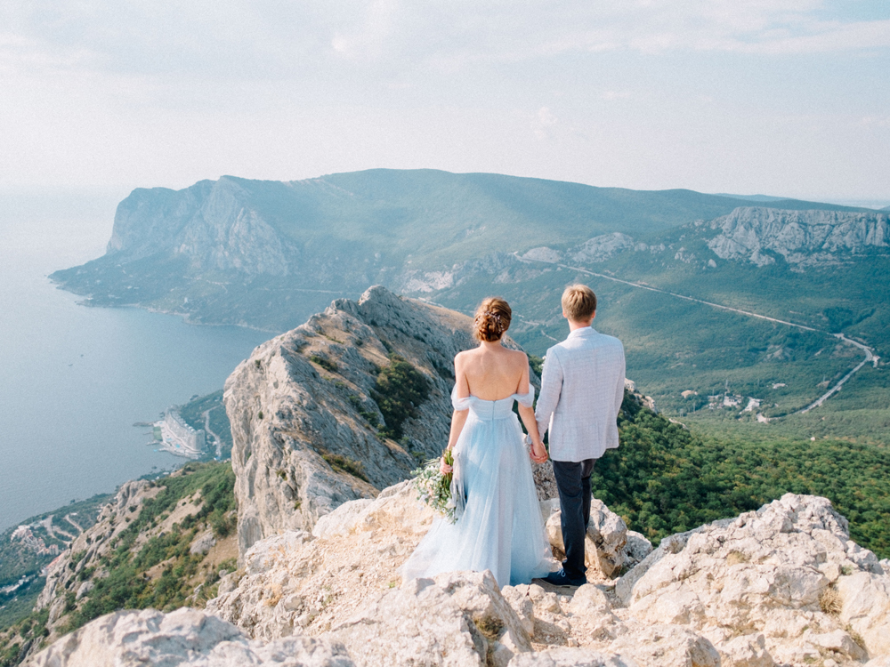 Bride in light blue off the shoulder dress standing on cliff in Europe with groom elopement