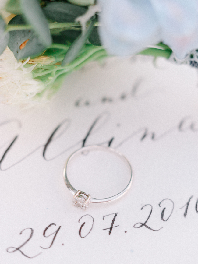 solitaire diamond engagement ring on calligraphy book elopement
