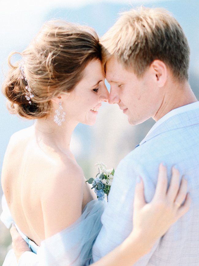 Bride and groom touch foreheads light blue manicure nails baby blue wedding dress hair updo earrings