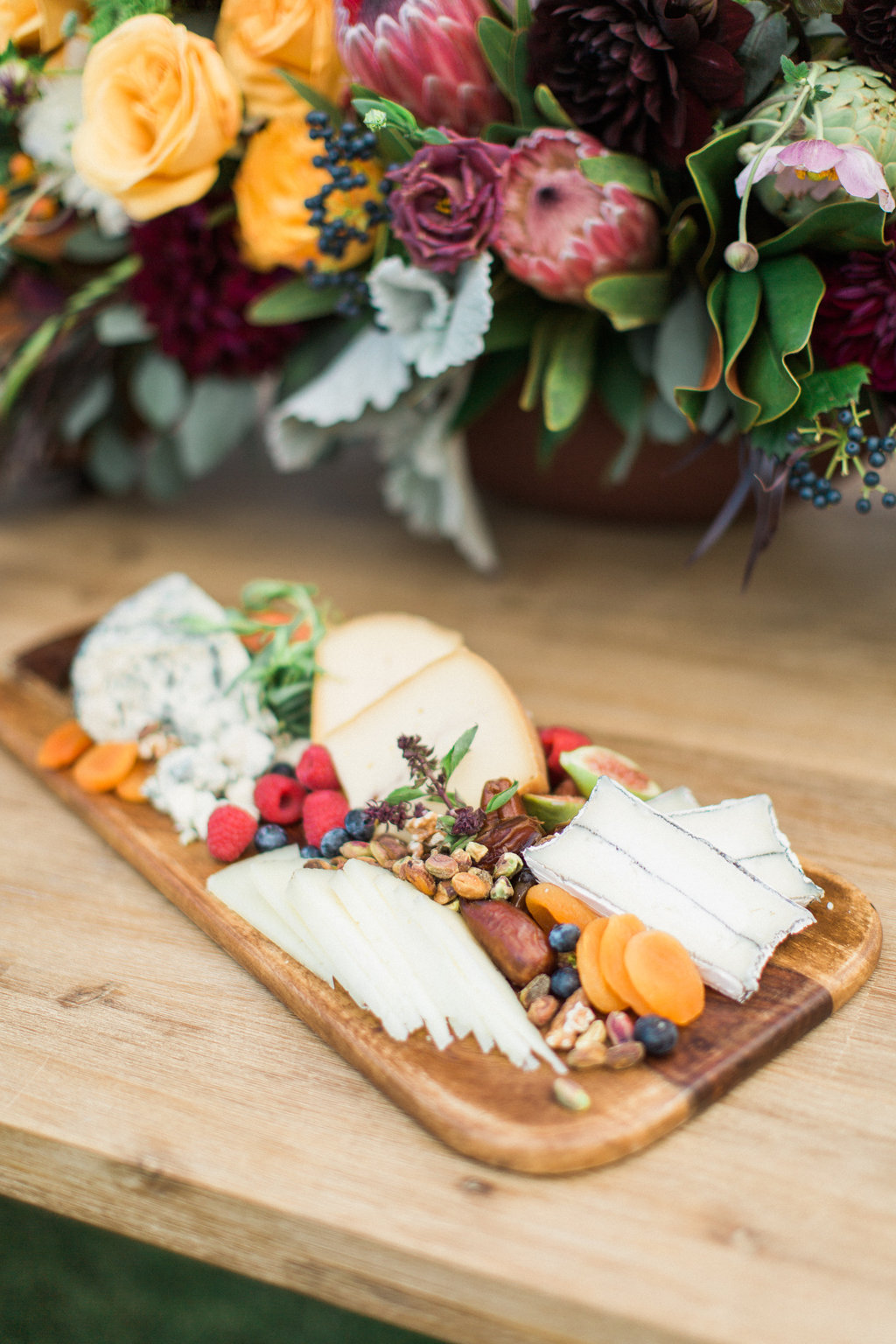 Cheese board on wood cutting board with dried fruits wedding reception styled shoot