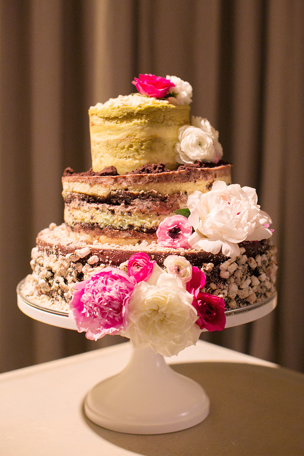 three-tiered multi-flavored naked cake with fresh flowers