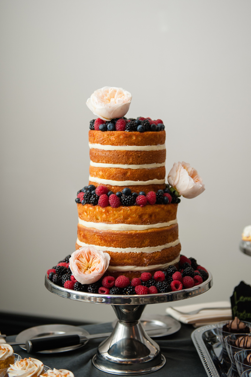 three-tiered naked wedding cake with berries and garden roses