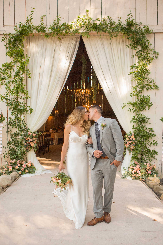Inside Weddings Spring 2017 issue bride in Ines Di Santo wedding dress in front of barn venue